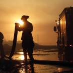 Del Mar firefighters roll up hose after a day fighting wildfires in Carlsbad, California.<span class=