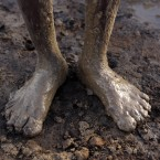 An Indian laborer''s legs are covered in mud as he works at a brick- manufacturing unit on the eve of International Labour Day in Chennai, India.<span class=