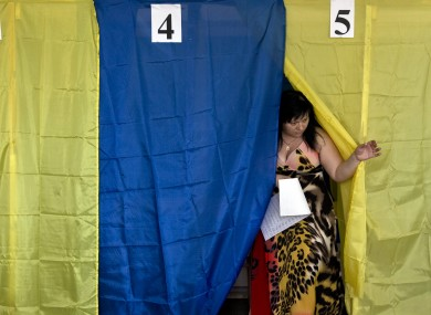 A woman exits a voting cabin after casting her vote in the presidential election in the eastern town of Krasnoarmeisk.