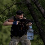 A pro-Russian gunman aims his weapon near the airport, outside Donetsk. Ukraine's military launched air strikes Monday against separatists who had taken over the airport in the eastern capital of Donetsk in what appeared to be the most visible operation of the Ukrainian troops since they started a crackdown on insurgents last month. <span class=