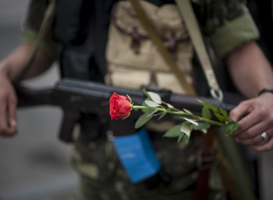 A pro-Russian fighter holds a gun and a rose after taking the oath of allegiance to the self-proclaimed Donetsk People's Republic