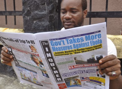 In Liberia, a man reads a newspaper with headlines reading 'Gov't Takes More Measures Against Ebola, as fear about the virus spread in the city of Monrovia.