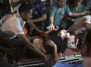 Medics wheel two wounded Palestinians into the emergency room of Shifa hospital in Gaza City.