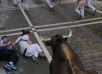Two people fall during the running of the bulls yesterday