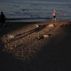 People swim on the seaside of Alimos near Athens.<span class=