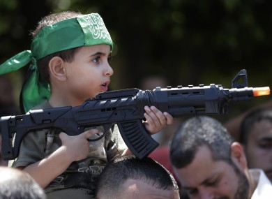 A Palestinian boy holds a toy gun at a Hamas rally in Gaza City today