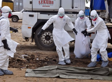 Health workers carry the body of a man found in the street, suspected of dying from the ebola virus, in the capital city of Monrovia, Liberia.