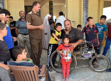 Displaced Iraqis wait for relief aid at a mosque on the outskirts of Irbil, northern Iraq, last week.