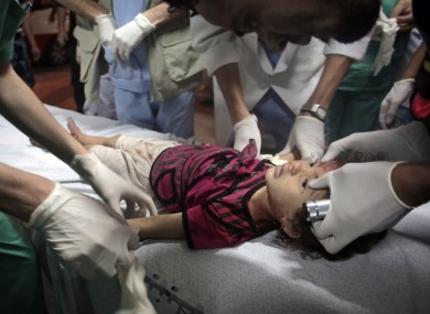 Palestinian medics treat a two-yea-old child  injured in an Israeli strike.