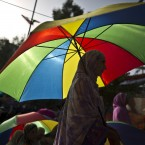 A supporter of fiery anti-government cleric Tahir-ul-Qadri, shelters herself from the sun under an umbrella, while waiting for his arrival to deliver a speech during a protest in Islamabad, Pakistan.<span class=