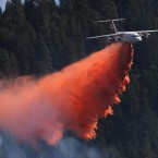 A jet aerial tanker drops its load of fire retardant on a fire near Pollack Pines, California.<span class=