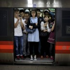 Commuters with their smartphones crowd inside a subway train during a rush hour in Beijing, China.<span class=