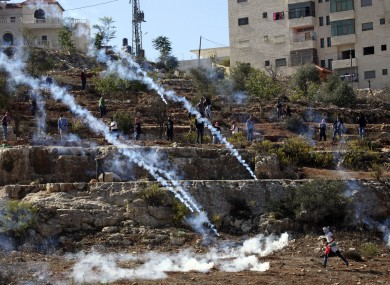 Palestinian protester runs from tear gas during clashes with security forces.