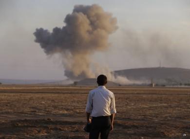 A Turkish Kurd watches as air strikes hit Kobane.