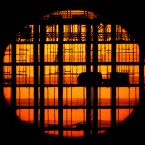 The sun sets beyond the shell of a building under construction.<span class=