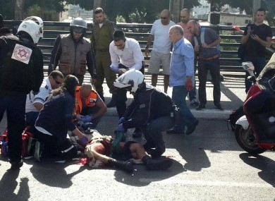 Paramedics treat an Israeli soldier after he was stabbed in Tel Aviv.