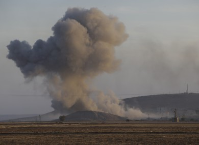 A huge plume of smoke rises after an airstrike in eastern Kobani, Syria, behind a hilltop where militants with the Islamic State group had raised their flag