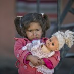 A girl holds a doll as refugees wait for the funeral convoy of 19 year-old Syrian Kurdish fighter girl Perwin Mustafa Dihap who died after being wounded during fighting against the Islamic State forces in her home town of Kobani, to pass by the camps in Suruc, on the Turkey-Syria border.<span class=