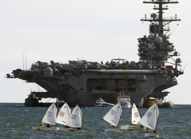Sail boats pictured beside the American aircraft carrier USS George HW Bush outside Piraeus port in Greece.