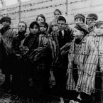 children wearing concentration camp uniforms behind barbed wire fencing as they were liberated from the Nazi concentration camp at Auschwitz.<span class=