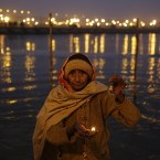 A Hindu pilgrim performs evening rituals at the Sangam, the confluence of the Rivers Ganges, Yamuna and mythical Saraswati, during the annual Magh Mela traditional fair in Allahabad, India, Saturday, Jan. 17, 2015. Hundreds of thousands of devout Hindus are expected to take holy dips at the confluence during the astronomically auspicious period of over 45 days celebrated as Magh Mela. (AP Photo/Rajesh Kumar Singh)<span class=