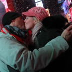 Dennis Brown, left, and his girlfriend Sheridan Nichols, of Johnson City, Tenn., kiss shortly after midnight in New York's Times Square <span class=