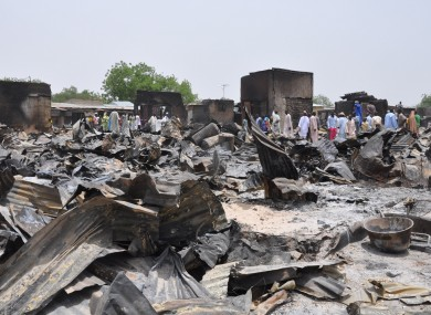 Nigerian people stand outside homes destroyed by Boko Haram. (FILE)