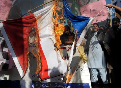Pakistani protesters burn a representation of a French flag during a protest against caricatures published in the French magazine Charlie Hebdo, in Peshawar.