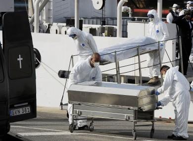 Italian Coast Guard officers disembark the body of a dead migrant off the ship Bruno Gregoretti.