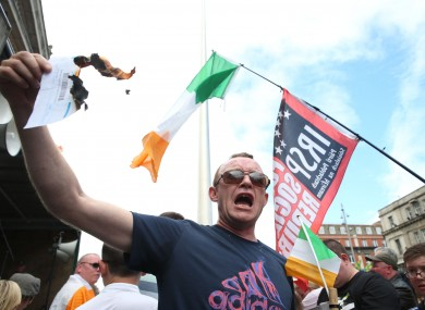 A protester burns a water bill on O'Connell Street during a demonstration against water charges in June.