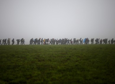 A group of migrants make their way over a meadow in Germany.