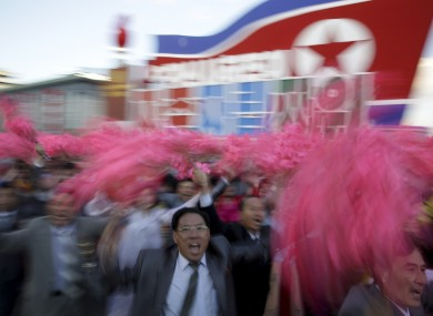 North Koreans wave decorative flowers as they parade in Pyongyang, North Korea.