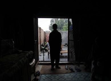 A victim of the child sex abuse scandal stands in his house in the Kasur district near Lahore, Pakistan.
