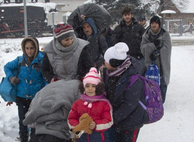 A group of migrants move through snow towards a train station to be transferred to Austria, near the border with Croatia, in Dobova, Slovenia,