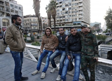 File photo: Syrian men pose for a picture as they gather in the Marjeh square in Damascus.