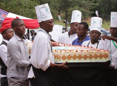 Chefs carry one of President Robert Mugabe's birthday cakes into the party venue.