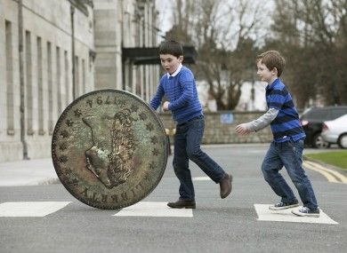 Six year olds Paddy Dwyer and William Hegarty from Foxrock and a replica of the coin. The real coin is much smaller.