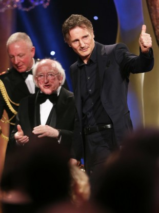 Liam Neeson giving the thumbs up after receiving the award from the President