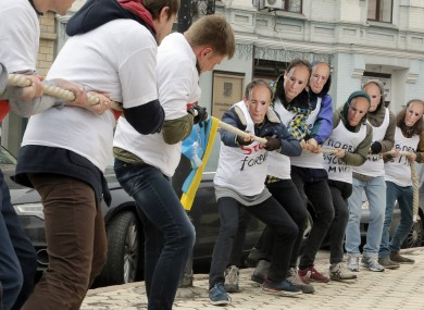 Activists, some wearing masks depicting Vladimir Putin, perform a tug of war in front of the Dutch embassy in Kiev.