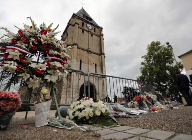 A wreath of flowers next to the church where an hostage taking left a priest dead.