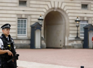 Armed police forces guard the entrance of Buckingham Palace in London today.