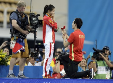 China's silver medalist He Zi, left, receivers a marriage proposal by China's diver Qin Ki, right, during the medal ceremony for the the women's 3-meter springboard diving final.
