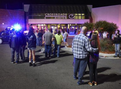 People stand near the entrance on the north side of Crossroads Center mall during the incident last night.