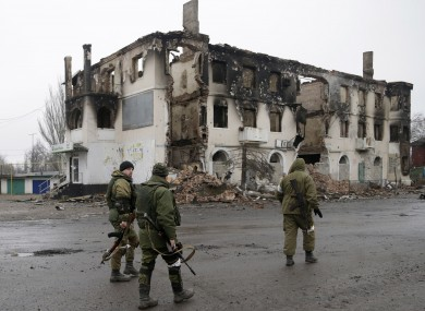 Russian-backed rebels walk past a destroyed building in the town of Vuhlehirsk in Ukraine last year.
