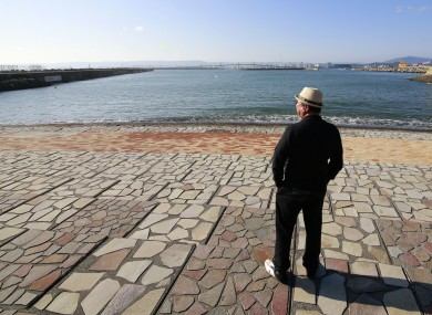 A man looks to sea after the tsunami warning was lifted at Onahama coastal region in Iwaki, in the Fukushima prefecture of northeastern Japan today.