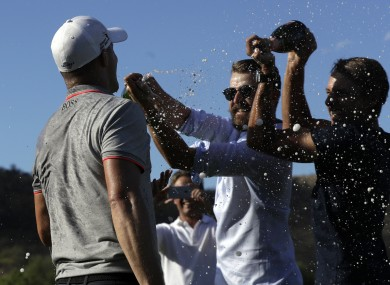 Noren is sprayed with champagne on the 18th green.