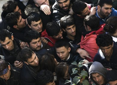 Migrants and refugees crowd in a line as they wait for their registration in Berlin, Germany, Thursday, Oct. 1, 2015.