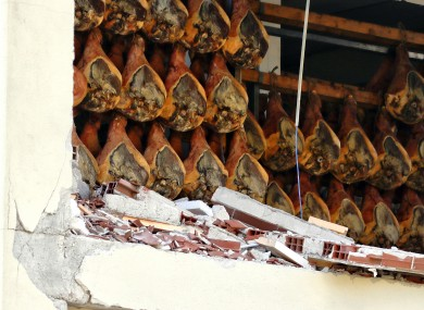 Cured hams hang in a damaged plant in Norcia, Italy.