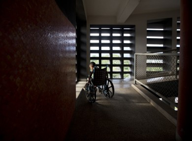 In this September 2016 photo, Marvin Osuna sits near a sunlit window in a passageway at University Hospital, in Caracas, Venezuela.