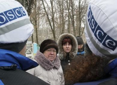 Local residents speak with OSCE monitors in Avdiivka, eastern Ukraine, yesterday.